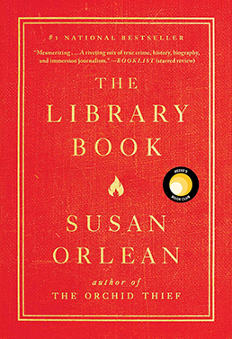 Cover - The Library Book by Susan Orlean. Bright Rea with double line gold frame around title and author name